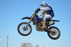 Il cavaliere di motocross salta, cielo blu Immagine Stock
