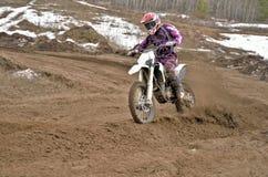 Il cavaliere di motocross su un motociclo guida accantonare immagine stock libera da diritti