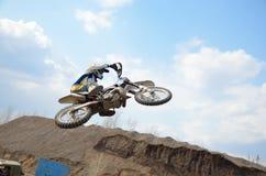 Il cavaliere di motocross vola orizzontalmente attraverso l'aria Fotografia Stock