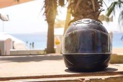 Il cavaliere nero misero del casco del motociclo in graffi sui precedenti del Mar Rosso e le palme sotto il sole per il posto man Fotografia Stock Libera da Diritti