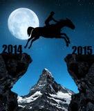 Il cavaliere sul cavallo che salta nel nuovo anno 2015 Fotografia Stock
