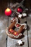 Il cavallo di natale del pan di zenzero con la cannella della candela stars la lampadina di natale del ramoscello del pino sul pa Fotografie Stock Libere da Diritti