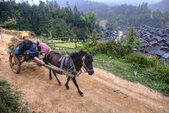 Il cavallo porta il vagone con i contadini asiatici, le donne agricoltori ed il bambino Immagini Stock