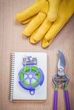 Il cavo del legame del pruner del giardino dei guanti di cuoio ha controllato il quaderno su legno b Fotografia Stock