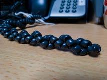Il cavo di telefono nero sulla tavola di legno e sul blackground vago del telefono fotografie stock libere da diritti