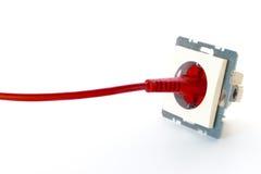 Il cavo elettrico rosso ha inserito lo sbocco di parete fotografia stock libera da diritti