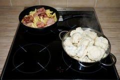 Il cavolfiore e la pasta sono cucinati su una cucina elettrica immagini stock