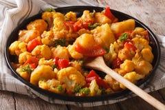 Il cavolfiore e le patate di Gobi Aloo si chiudono su su un piatto horizont Fotografia Stock