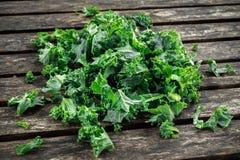 Il cavolo di verdure del superfood sano verde fresco va sulla tavola rustica di legno Immagine Stock