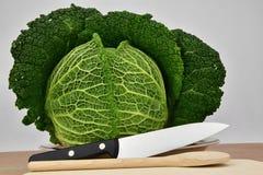Il cavolo su un piatto sul tagliere della cucina è un coltello e un cucchiaio di legno Immagini Stock Libere da Diritti