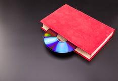 Il CD è attacca fuori dal libro rosso Immagine Stock