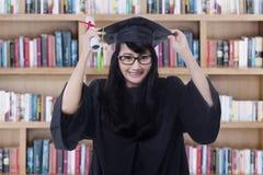 Il celibe allegro celebra la graduazione in biblioteca Fotografie Stock Libere da Diritti