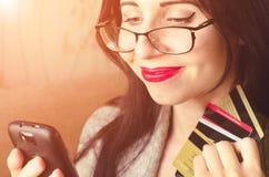 Il cellulare caucasico sorridente app di usi della ragazza, tiene le carte e compra qualcosa fotografie stock