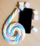 Il cellulare e una caramella gommosa e molle lunga hanno rotolato su un numero 6 Fotografia Stock