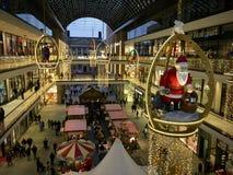 Il centro commerciale di Berlino ha decorato per il Natale con grande Santa Claus di legno, occupato con molti clienti immagine stock libera da diritti