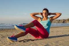 Il centro di addestramento della donna di forma fisica con la bicicletta sgranocchia l'esercizio Immagini Stock