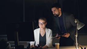 Il CEO della società sta parlando con suo segretario che lavora con le ore tarde del computer che danno gli ordini e che discuton archivi video
