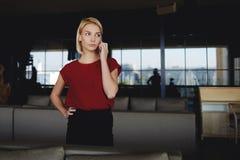 Il CEO femminile arrabbiato si è vestito nell'usura convenzionale che chiama con il telefono cellulare ai suoi colleghi che sono  Immagine Stock