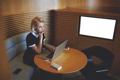 Il CEO femminile con il computer portatile sta sedendosi nello spazio in bianco vicino interno dello schermo dell'ufficio moderno Immagine Stock