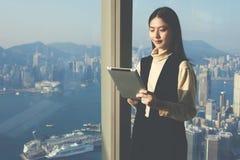Il CEO femminile con il cuscinetto di tocco sta stando nell'interno di lusso dell'ufficio del grattacielo Fotografia Stock Libera da Diritti