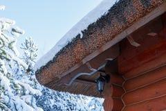 Il ceppo di legno ha ricoperto di paglia il tetto coperto in neve nell'inverno Fotografia Stock