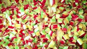 Il cereale di caramella piccolo del caramello riempie lo schermo che cade sulla tavola nella fabbricazione del caramello video d archivio