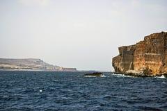 Il chiaro mar Mediterraneo blu che spruzza contro le rocce del mare con il chiaro cielo blu immagini stock