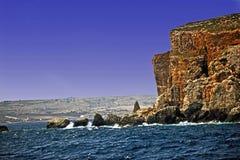 Il chiaro mar Mediterraneo blu che spruzza contro le rocce del mare con il chiaro cielo blu fotografia stock libera da diritti