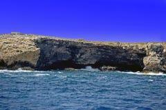 Il chiaro mar Mediterraneo blu che spruzza contro le rocce del mare con il chiaro cielo blu fotografia stock