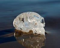Il chiaro quarzo ha scolpito lo straniero maya prolungato Crystal Skull che mette sulla sabbia bagnata all'alba immagine stock