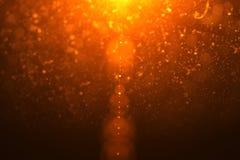 Il chiarore leggero dorato astratto cola con le particelle dell'oro fotografie stock