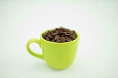 Il chicco di caffè in tazza verde, fondo bianco, fuoco selettivo immagini stock libere da diritti