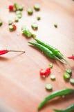 Il chilie verde e rosso tagliato pepa su un bordo di legno Fotografie Stock