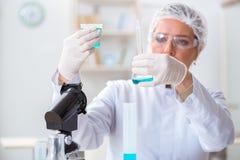 Il chimico della donna che lavora nel laboratorio della clinica dell'ospedale Immagine Stock