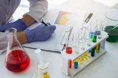 Il chimico dello scienziato prende le note con una soluzione chimica liquida rossa che fa la prova o la ricerca in laboratorio Immagine Stock
