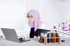 Il chimico lavora con il computer portatile e la lavagna per appunti Immagini Stock