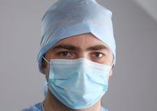Il chirurgo dell'uomo tiene un bisturi in una sala operatoria Fotografie Stock