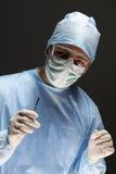 Il chirurgo dell'uomo tiene un bisturi in una sala operatoria Immagini Stock