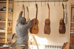 Il chitarra-creatore professionale serio prende con la chitarra non finita all'officina Immagini Stock