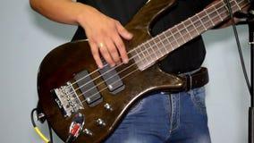 Il chitarrista gioca su un basso marrone in studio, vestito in jeans ed in una camicia nera archivi video