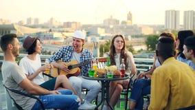 Il chitarrista maschio sta giocando la chitarra mentre i suoi amici sono cantanti, ridenti e beventi la birra e le bibite a video d archivio