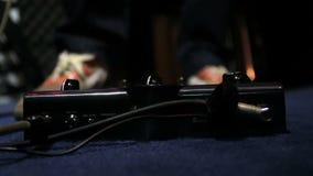 Il chitarrista preme con il suo piede sul pedale di effetti - premi una volta sul pedale video d archivio