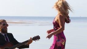 il chitarrista smette di giocare le fermate bionde della ragazza che ballano sulla spiaggia video d archivio