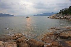 Il ciarpame cinese in Hong Kong innaffia con una riviera rocciosa verso la fine del pomeriggio Immagini Stock