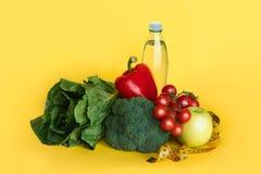 Il cibo sano, essendo a dieta, dimagrendo e pesa il concetto di perdita Verdure, acqua e nastro di misurazione su fondo giallo fotografie stock