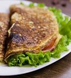 Il cibo sano per la prima colazione ha rimescolato le uova con la farina d'avena, prosciutto e formaggio, lattuga e pomodori dent Immagini Stock Libere da Diritti