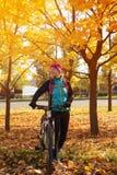 Il ciclista allegro della donna nel parco di autunno sta stando sul BAC Immagine Stock Libera da Diritti