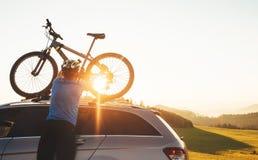 Il ciclista dell'uomo veared in vestiti di riciclaggio ed in casco protettivo installa il suo mountain bike sul tetto dell'automo immagine stock