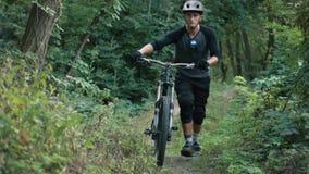 Il ciclista estremo viene con la bicicletta in foresta archivi video
