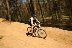 Il ciclista fa concorrenza nella corsa dell'elite MTB alla foresta Immagine Stock
